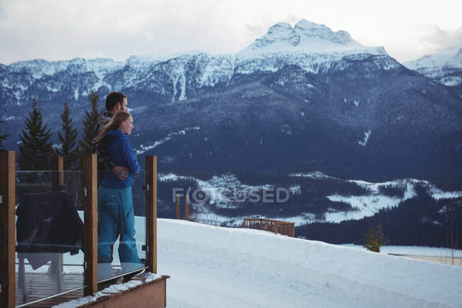 Couple embracing while standing by railing against snow capped mountains — Stock Photo