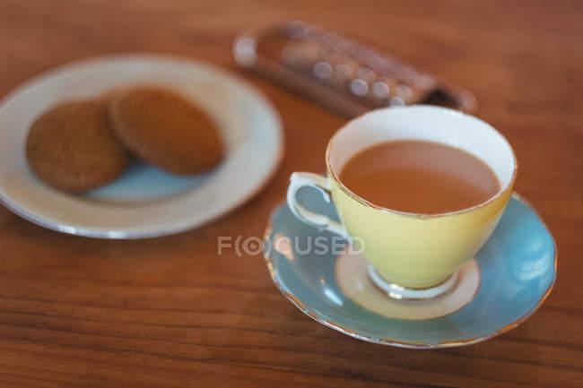 Gros plan du thé avec les cookies sur table en bois — Photo de stock