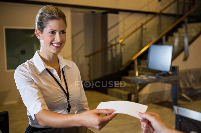Personal femenino dando boleto al pasajero en la terminal del aeropuerto - foto de stock