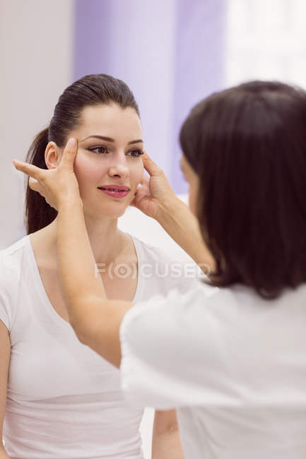 Дерматолога, вивчаючи жіночий шкіри пацієнта в клініку — стокове фото
