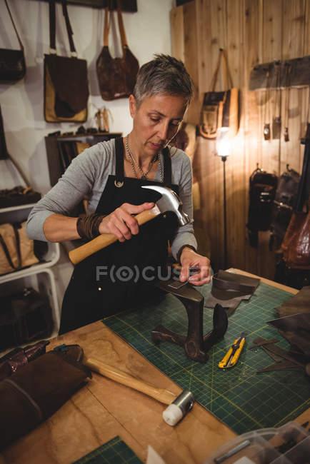 Craftswoman martelando couro no interior da oficina — Fotografia de Stock