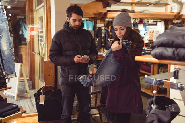 Woman selecting apparel in a clothes shop while man using mobile phone — Stock Photo