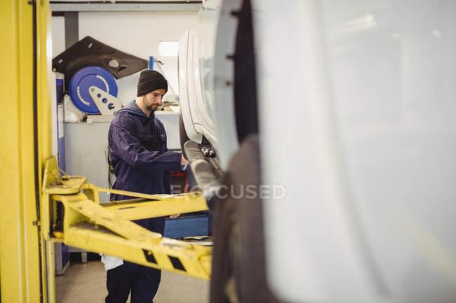 Механік вивчення машину в ремонт гаража — стокове фото
