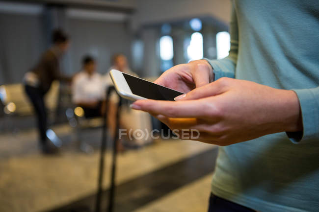 Mid-section of woman using mobile phone in airport terminal — Stock Photo