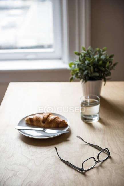 Завтрак с растением в горшке и зрелище на столе дома — стоковое фото
