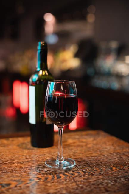 Крупный план бокала красного вина на стойке бара в баре — стоковое фото