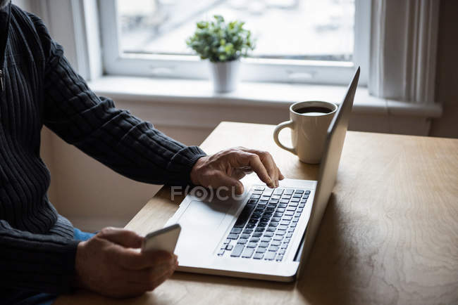 Mid-section of man using laptop and mobile phone at home — Stock Photo