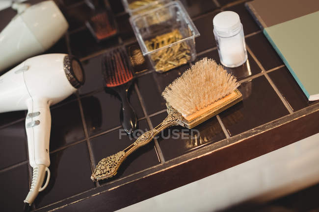 Close-up of hairbrush and hairdryer in salon — Stock Photo