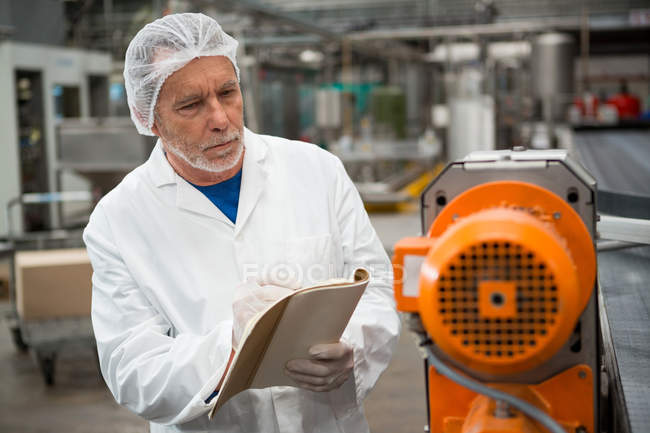 Serious male worker inspecting machines at cold drink factory — Stock Photo