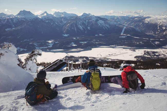 Три лыжников расслабляющий на снежный пейзаж зимой — стоковое фото