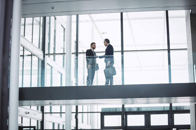 Businessman greeting a colleague in corridor of an office building — Stock Photo
