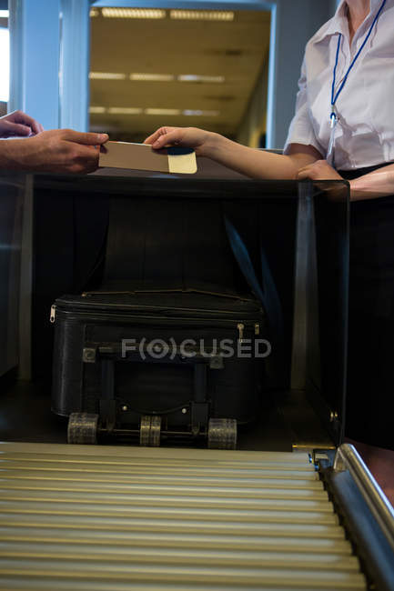 Seção intermediária de funcionários do sexo femininos, dando o cartão de embarque para o cheque na mesa — Fotografia de Stock
