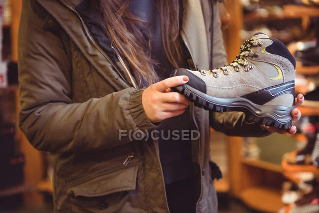 Close-up of woman selecting shoe in a shop — Stock Photo