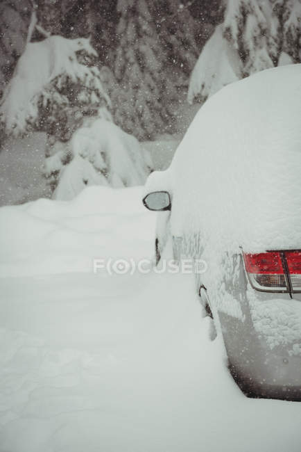 Coche cubierto de nieve durante el invierno - foto de stock