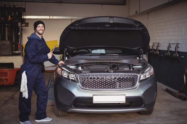 Meccanico sorridente e tenendo in mano uno strumento chiave in garage di riparazione — Foto stock