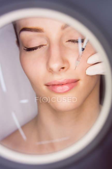 Молодая пациентка получает косметическую инъекцию на лице в эстетической клинике — стоковое фото