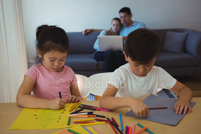 Boy and girl drawing in paper while parents using laptop in background at home — Stock Photo