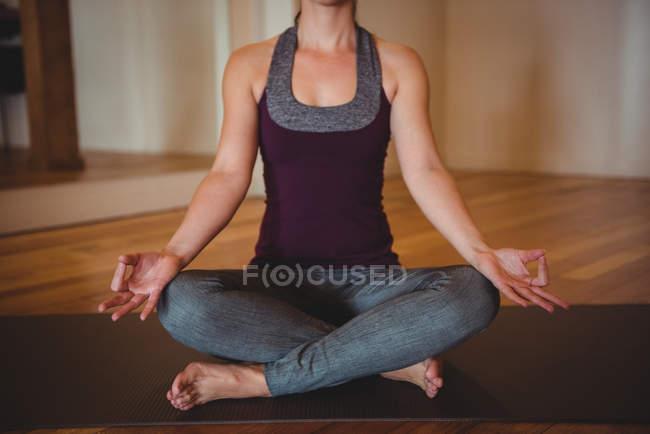 Здоровая женщина, практикующая йогу в фитнес-студии — стоковое фото