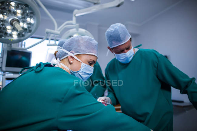 Group of surgeons performing operation in operation theater of hospital — Stock Photo