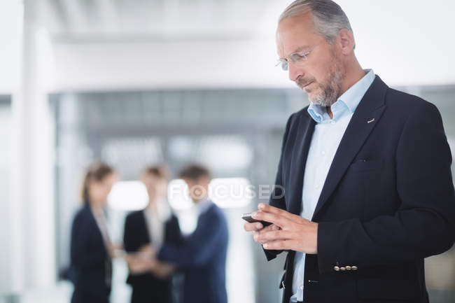 Businessman using mobile phone inside office building — Stock Photo