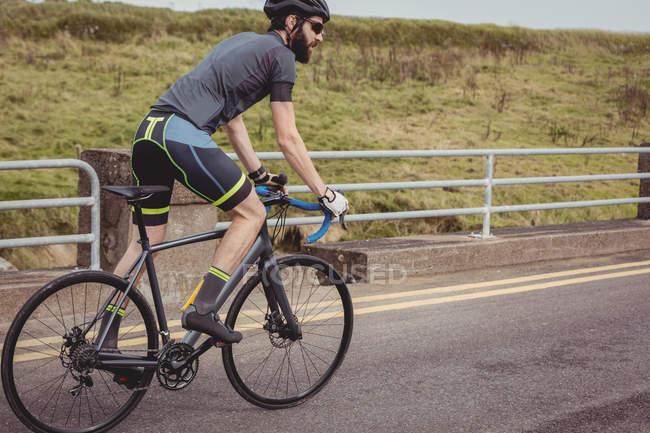 Спортсмен їздового спорту велосипеді по сільська дорога — стокове фото