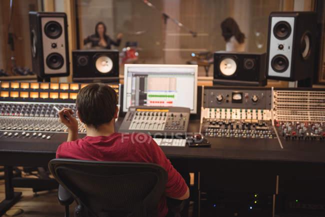 Audio engineer working on sound mixer in recording studio — Stock Photo