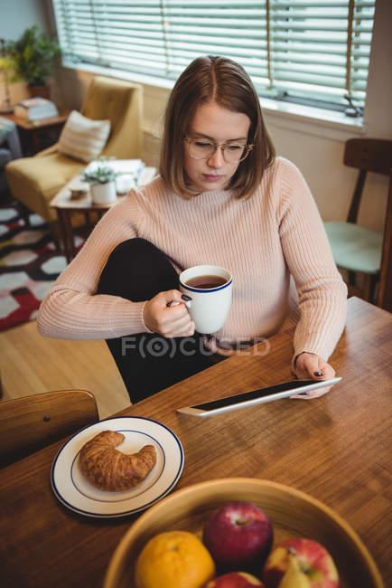 Donna che utilizza tablet digitale mentre tiene in mano la tazza di caffè a casa — Foto stock