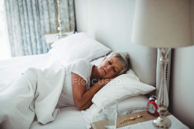 Старші жінки, лежачи на ліжку в спальні в домашніх умовах — стокове фото