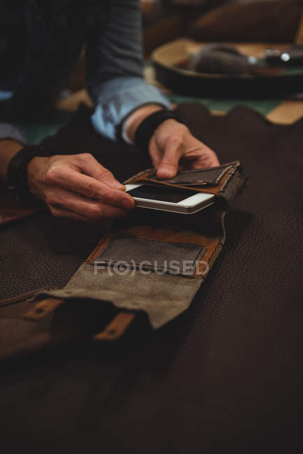 Craftswoman preparando capa de couro para celular na oficina — Fotografia de Stock