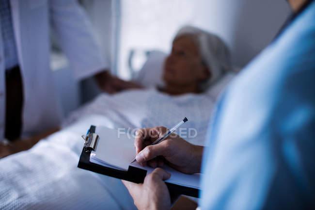 Doctor masculino escribir una receta en un portapapeles en el hospital - foto de stock