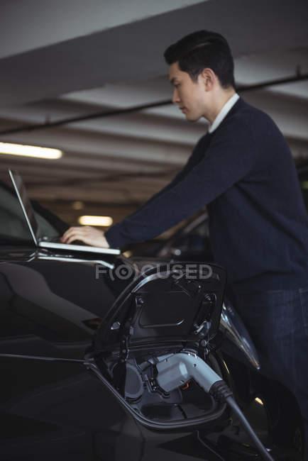 Homme utilisant un ordinateur portable tout en chargeant une voiture électrique dans le garage — Photo de stock