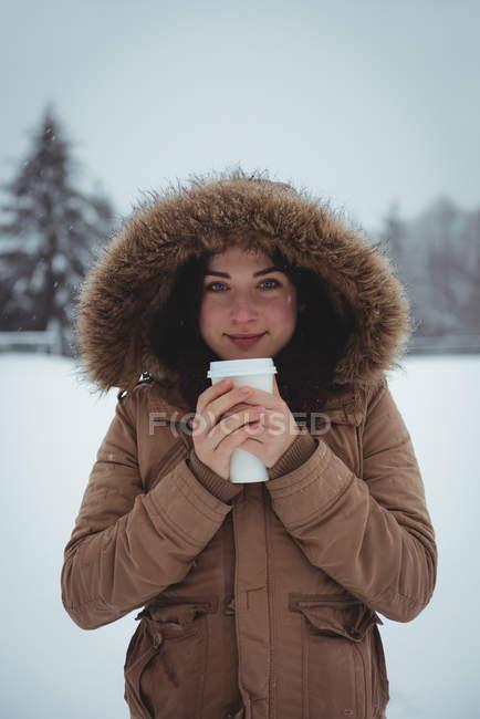 Портрет улыбающейся женщины в меховой куртке, пьющей кофе зимой — стоковое фото