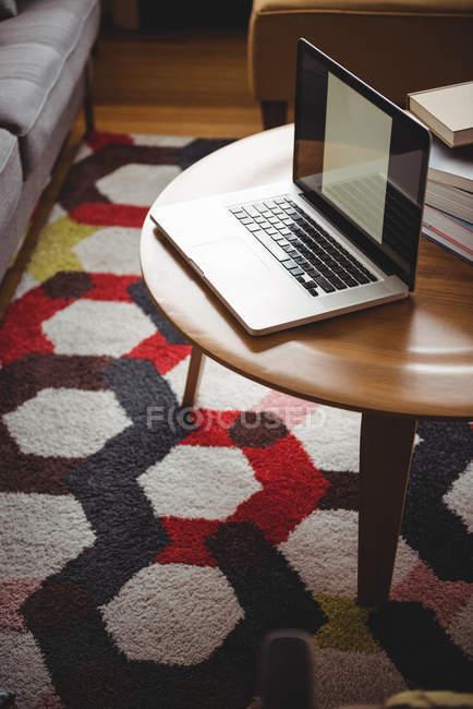 Laptop su tavolo in legno in soggiorno a casa — Foto stock
