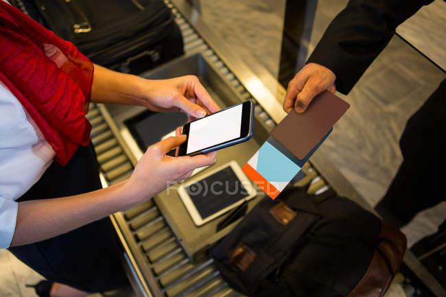 Close-up da fêmea de verificação do cartão de embarque com telefone móvel — Fotografia de Stock