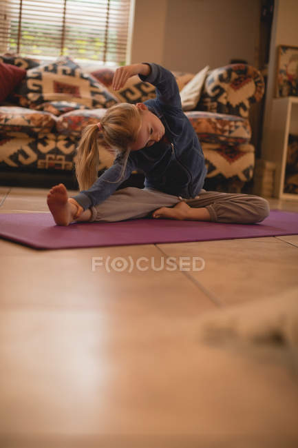 Girl performing yoga stretching exercise in living room at home — Stock Photo