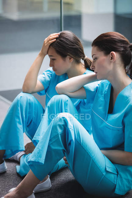 Sad nurses sitting on corridor in hospital — стоковое фото