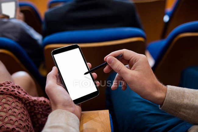 Бизнес-руководители, участвующие в деловой встрече с использованием мобильного телефона в конференц-центре — стоковое фото