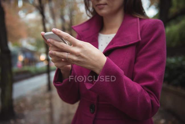 Vista ritagliata di donna d'affari utilizzando il telefono mentre in piedi sul percorso — Foto stock