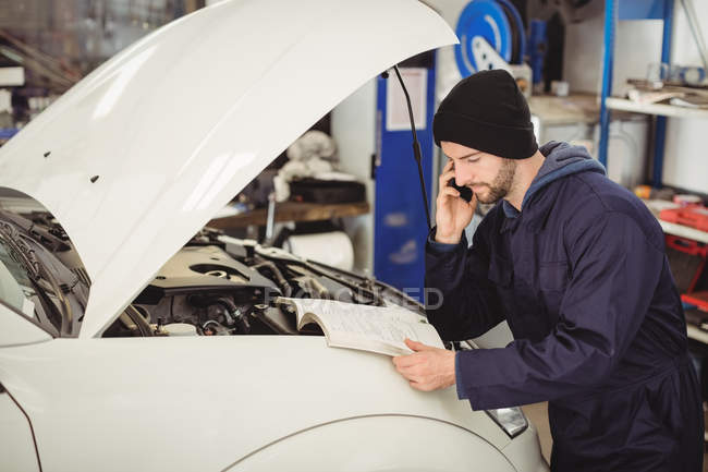 Mechanic reading instruction manual while talking on mobile phone at repair  garage — phone call, working - Stock Photo | #225323982