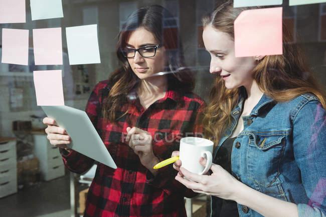 Керівників бізнесу, обговорюючи над цифровий планшетний маючи каву в офісі — стокове фото