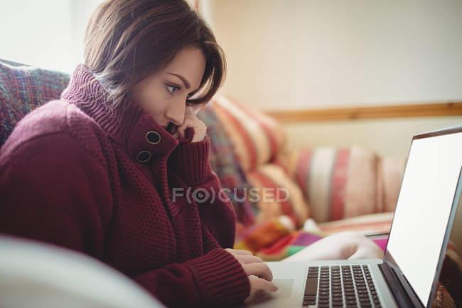 Schöne Frau mit Laptop auf dem Sofa zu Hause — Stockfoto