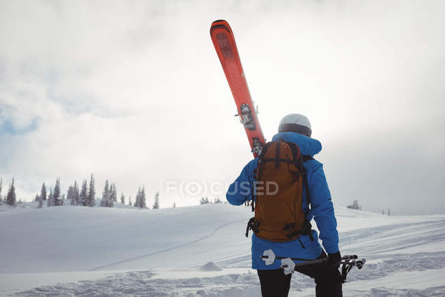 Rear view of skier walking with ski on snow covered mountain — Stock Photo