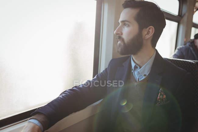 Un uomo d'affari premuroso che guarda fuori dal finestrino del treno — Foto stock