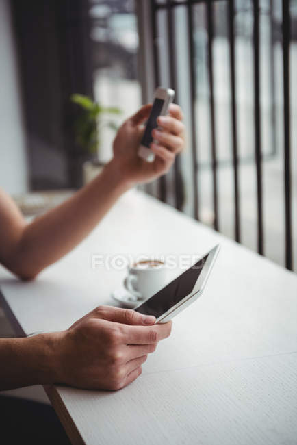 Hands of man holding mobile phone and digital tablet — Stock Photo