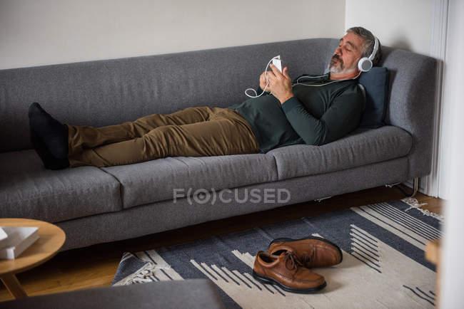 Mann hört zu Hause Musik auf Handy — Stockfoto