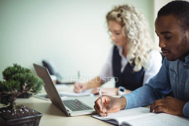 Dirigeants d'entreprise prenant des notes tout en utilisant un ordinateur portable au bureau — Photo de stock