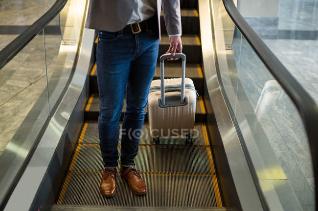 Low section of businessman standing on escalator with luggage at airport — Stock Photo