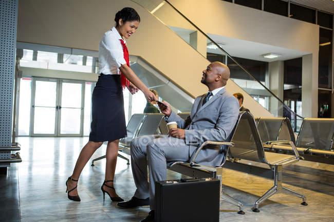 Бизнесмен, выдающий паспорт в зале ожидания авиакомпании в аэропорту — стоковое фото