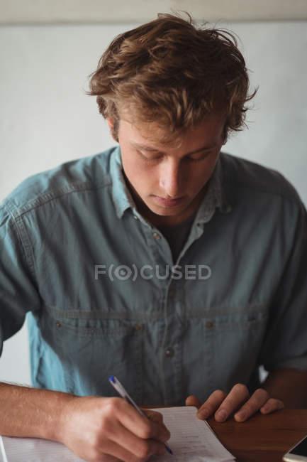 Людина сидить в бюро, писати на ноутбук на дому — стокове фото