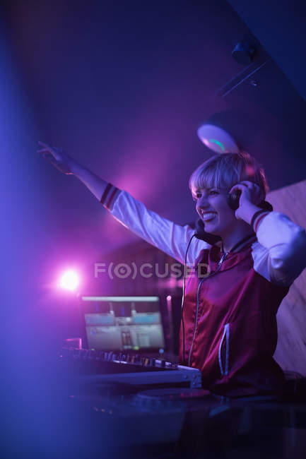 Pretty female dj waving while playing music in bar — Stock Photo